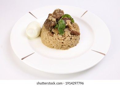 Beef Biryani Tehari cooked in mustered oil with boiled egg coriander leaf garnish on white plate over white background - Shutterstock ID 1914297796