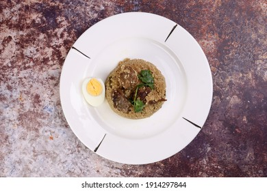 Beef Biryani Tehari cooked in mustered oil with boiled egg coriander leaf garnish on white plate over rustic rustic marble stone background - Shutterstock ID 1914297844