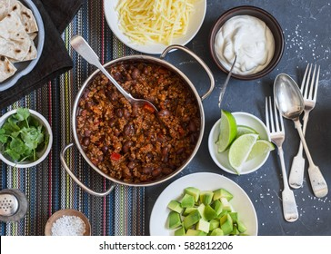 Beef and black bean chili bar on dark background, top view. Flat lay
