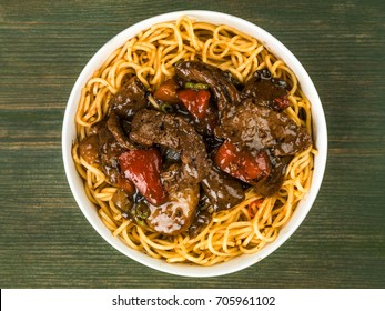 Beef and Black Bean Sauce With Red Peppers And Egg Noodles Against A Green Wooden Background