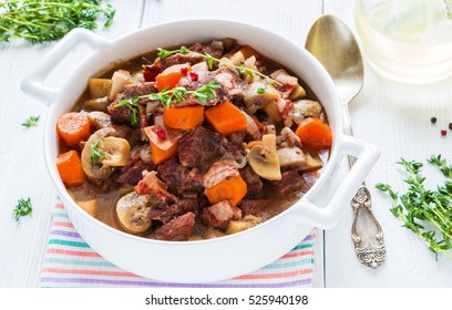 Beef Bourguignon in a casserole on white table. Stewed with bacon, garlic, carrots, onions, mushrooms,  and spices. Bunch of fresh thyme, vintage spoon, red wine.
