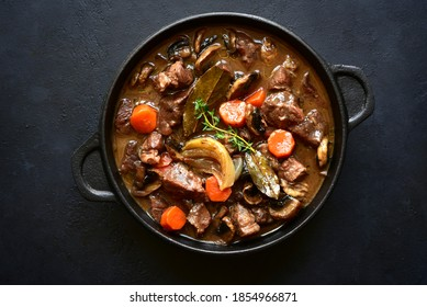Beef bourguignon - meat stew with vegetables and mushrooms with red wine in a skillet over black slate, stone or concrete background , traditinal dish of french cuisine. Top view with copy space.