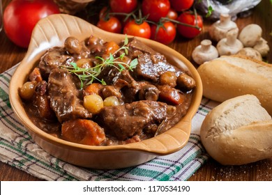 Beef Bourguignon stew served with baguette on dish. French cuisine