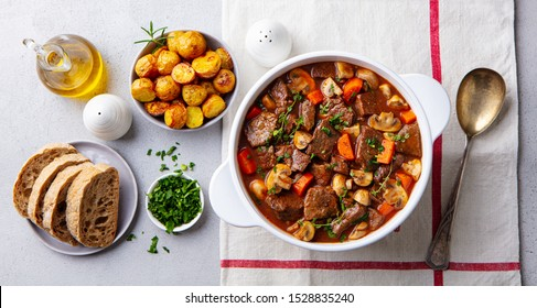 Beef bourguignon stew with vegetables. Grey background. Top view.