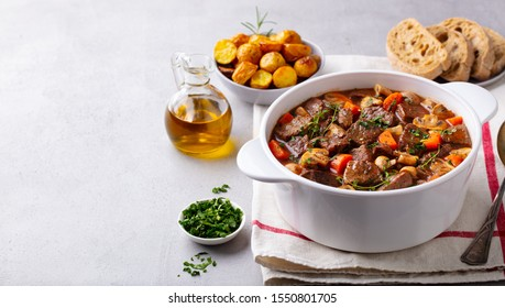 Beef bourguignon stew with vegetables. Grey background. Copy space.