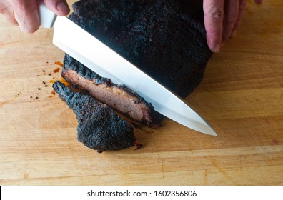 Beef Brisket. Traditional Classic style Texas Beef Brisket Barbecue staple. Slow cooked, roast rump rubbed in herbs and spices, in a smokehouse over mesquite wood chips. Action shots of slicing meat