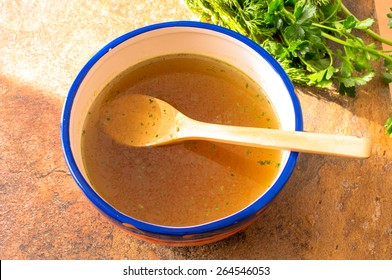 Beef broth with herbs and wooden spoon top view