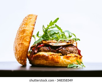 Beef burger with camembert and arugula on white background