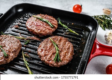 Beef burger patties sizzling on a hot barbecue pan. White background. Top view