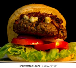 Beef Burger Topped with Blue Cheese and Caramelized Onions Set On A Toasted Bun with Lettuce Tomato Onion