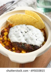 Beef burger topped with melt cheese, corn and bean garnish, and corn chips in a rustic pot