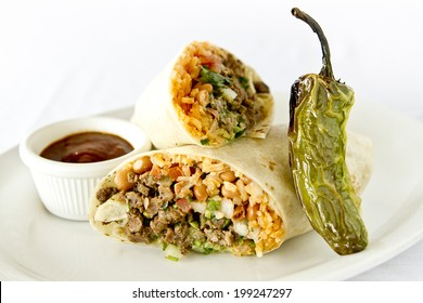 A beef burrito with beans and rice cut in half.