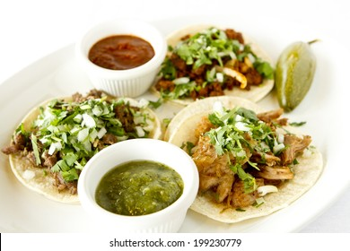 A beef, carnitas, and chicken taco with salsas.