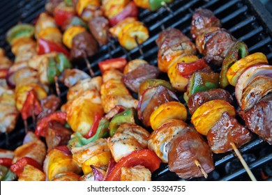 Beef and chicken kebabs cooking on a BBQ