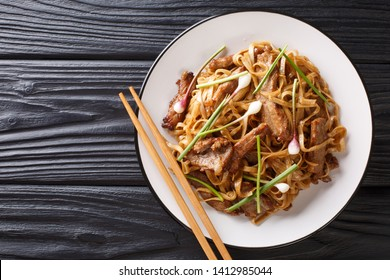 Beef Chow Fun a staple Cantonese dish, made from stir-frying beef, wide rice noodles and vegetables closeup on the plate on the wooden table. Horizontal top view from above
