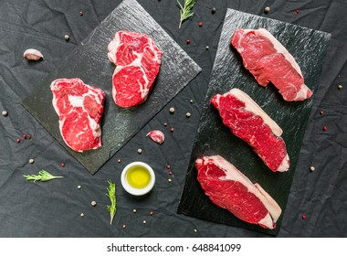 Beef cow steak meat with spices and herbs against black background