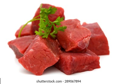 beef cubes with parsley on white background