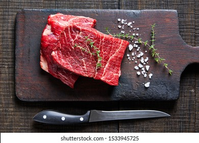 Beef cut: raw flat iron steaks of corn-fed cows on a dark wooden cutting board on a dark wooden background with fresh rosemary, sea salt, olive oil, peppercorns, garlic, view from above