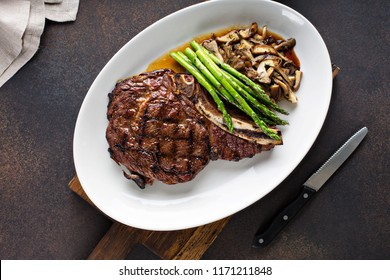 Beef eye of a round steak with asparagus and mushrooms