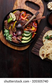 Beef fajita with bell peppers. Tortillas, avocado, sauce served with grilled beef and vegetables on skillet. Tex-mex cuisine