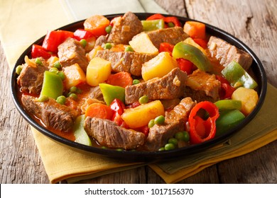 Beef filipino caldereta with vegetables close-up on a plate on the table. horizontal