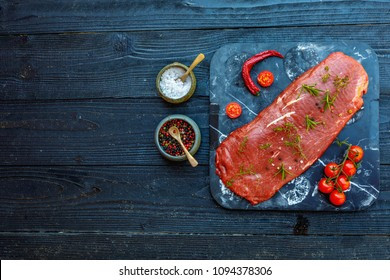 Beef Flat Iron steak on old metallic smoke stone tray on gray concrete background, top view, copy space