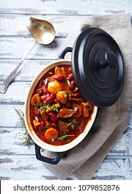 Beef Goulash with Kidney Beans, Carrot, Champignon Mushrooms, Onion and Fresh Herbs. Rustic wooden background. Top view. Copy space.