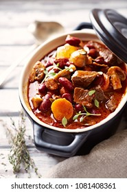 Beef Goulash with Kidney Beans, Carrot, Champignon Mushrooms, Onion and Fresh Herbs. Rustic wooden background.  Close up.