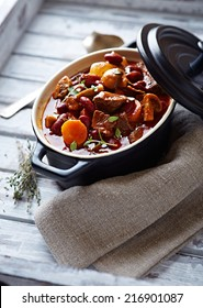 Beef goulash with mushrooms and vegetables. Symbolic image. Concept for a tasty and hearty dish. Bright wooden background.