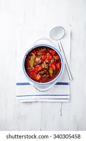 Beef goulash with pepper and mushrooms. Rustic wooden background. Top view. Copy space.