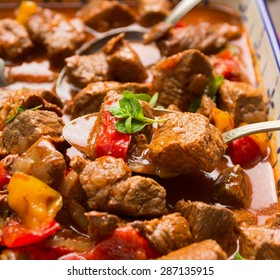 Beef goulash with vegetables and spoon, close up