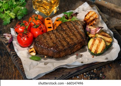 Beef grilled steak with set of grilled vegetables and glass of whiskey on wooden table close up beef