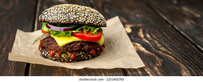 Beef hamburger with black bun with lettuce and ketchup served on a rustic wooden table