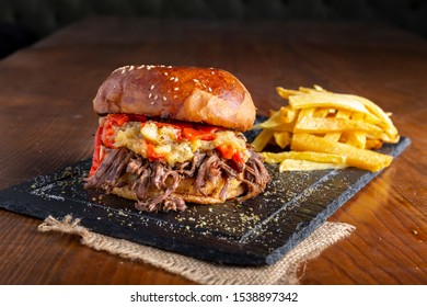 Beef Hamburger Sandwich with aubergine paste, corn beans, pickles, sliced mushroom, red belly pepper and fried french fries on wooden table. Copy space for text area.