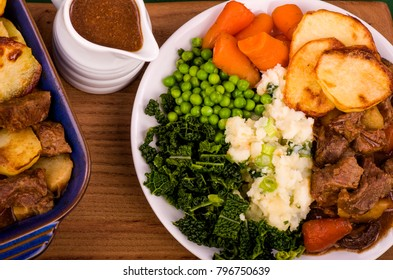 Beef in Irish Stout Stew A dish of Beef in Irish stout with a topping of sliced potatoes, served with a selection of vegetables and Sourdough bread, with stout battered onion rings and a jug of onion