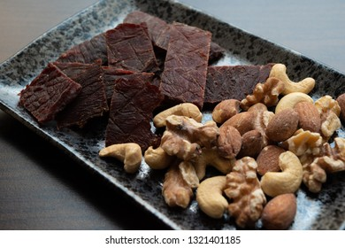 Beef jerky and nuts on the plate