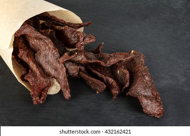 Beef jerky on a slate plate close-up