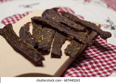 Beef jerky on wooden board and rustic rag