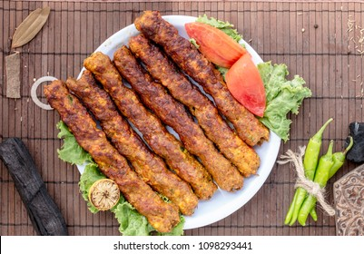 Beef kababs on a white plate with vegetables garnishing on it, top view