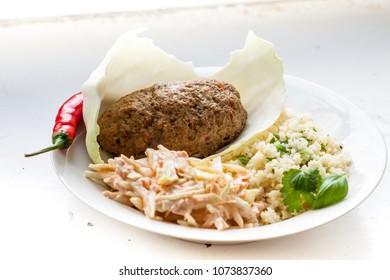 Beef kofta with fresh onion chilipepper coriander basil garlic pepper salt , plus couscous and coleslaw salad.