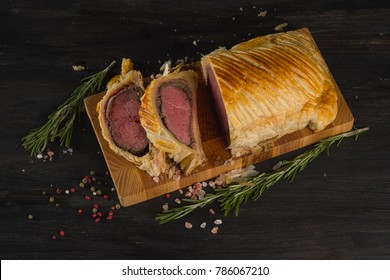 Beef meat cooking or boeuf en crout cut into slices on a chopping board black background. Top flat view, from above.