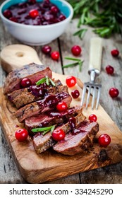 beef meat with homemade cranberry sauce on a rustic background