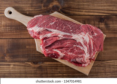 Beef meat on cutting board and wooden background