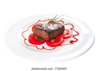 beef meat served on white plate with tomato