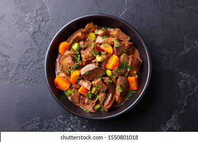 Beef meat and vegetables stew in black bowl. Slate background. Top view.