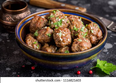 Beef meatballs in a bowl with sauce, brown with sesame and parsley, delicious snack