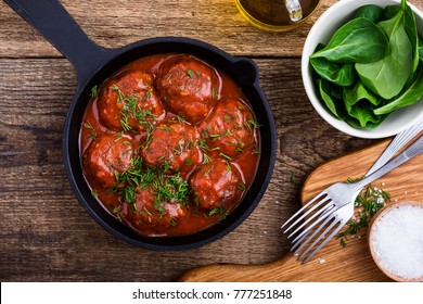 Beef meatballs in cast iron skillet with tomato sauce served with fresh spinach salad on rustic wooden table, top view