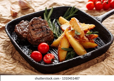 Beef Medallion Grill Roast Country Potato Closeup on Rustic Black Pan Serving for Delicious Recipe. Pork Fillet Cooked on Skillet for Dinner with Rosemary and Salt. Fried Juicy Meat Texture