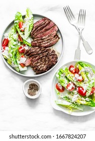 Beef medium rare steak and lettuce cherry tomatoes yogurt dressing salad on a light background, top view
