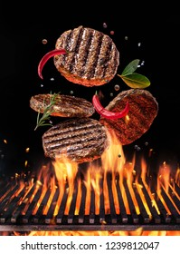 Beef milled meat on hamburger with spices fly over the flaming grill barbecue fire. Concept of flying food.